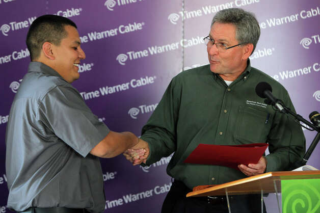 Agustin Arreguin (left), a Time Warner Cable repair technician who revived a 7-year-old who nearly drowned in a North Side apartment pool Tuesday evening, receives a certificate of recognition for extraordinary personal action from Mike Bennett, CEO of the American Red Cross, as he was honored by Time Warner and the American Red Cross for his heroic act during an award ceremony at Time Warner's San Antonio headquarters on July 29, 2011. Photo: Jennifer Whitney / Special to the Express-News