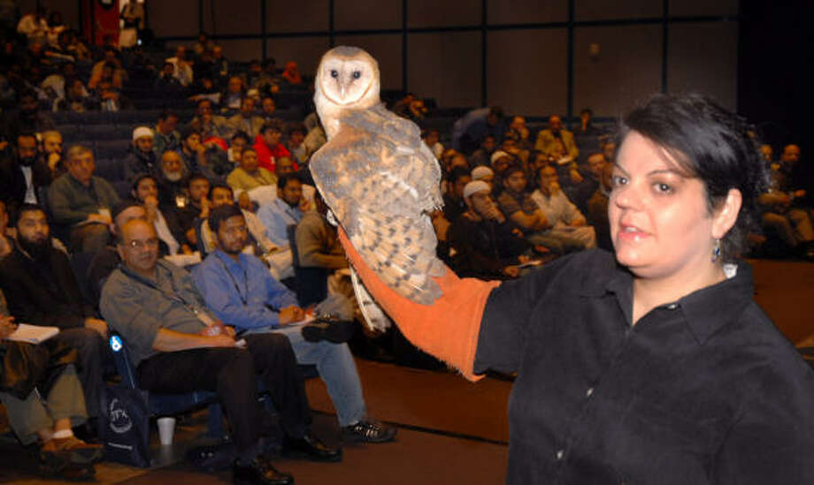 "Eliscia Jinkins of Wildlife Rehab & Education displays a barn owl Saturday at the Texas Dawah convention at the George R. Brown Convention Center. The Quran teaches Muslims to appreciate animals' beauty, ""and that brings you closer to God,"" lecturer Sheik Yasir Qadhi said. Photo: Dave Rossman, For The Chronicle"