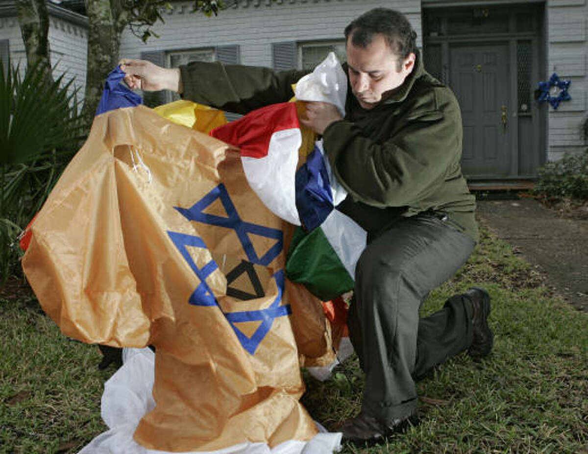 Brian Cweren displays a damaged, inflatable menorah cut in the front yard of his Meyerland-area home. Martin Cominsky, the head of the Houston Anti-Defamation League, is concerned about menorah vandalism incidents in Houston and Fort Bend County.