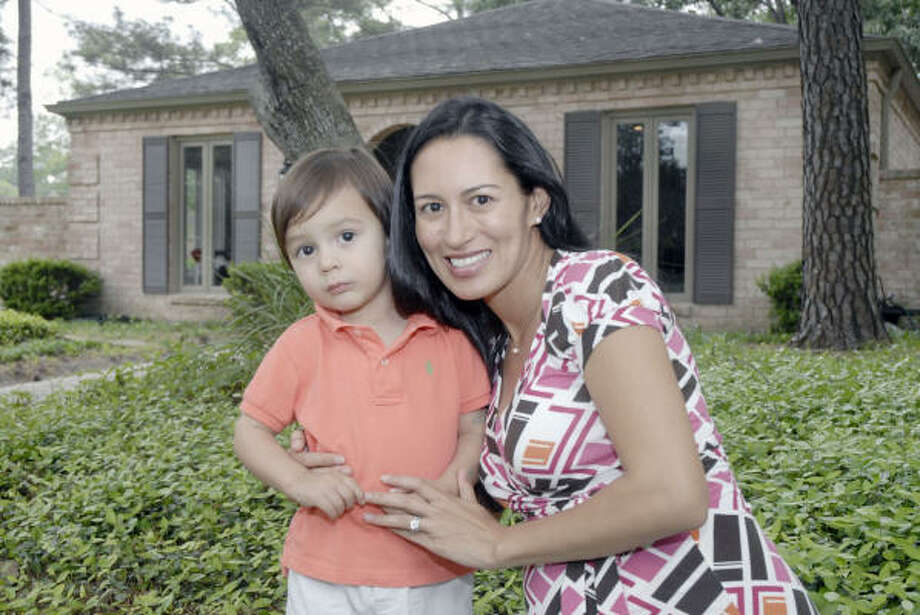 """AnaLitza Factor, who poses with her son Ben, 2, said she and her husband, Justin, were instantly attracted to the Briargrove Park neighborhood. """"We liked the neighborhood's charm. Each house has its own personality and is not cookie-cutter."""" Photo: Tim Johnson, For The Chronicle"""