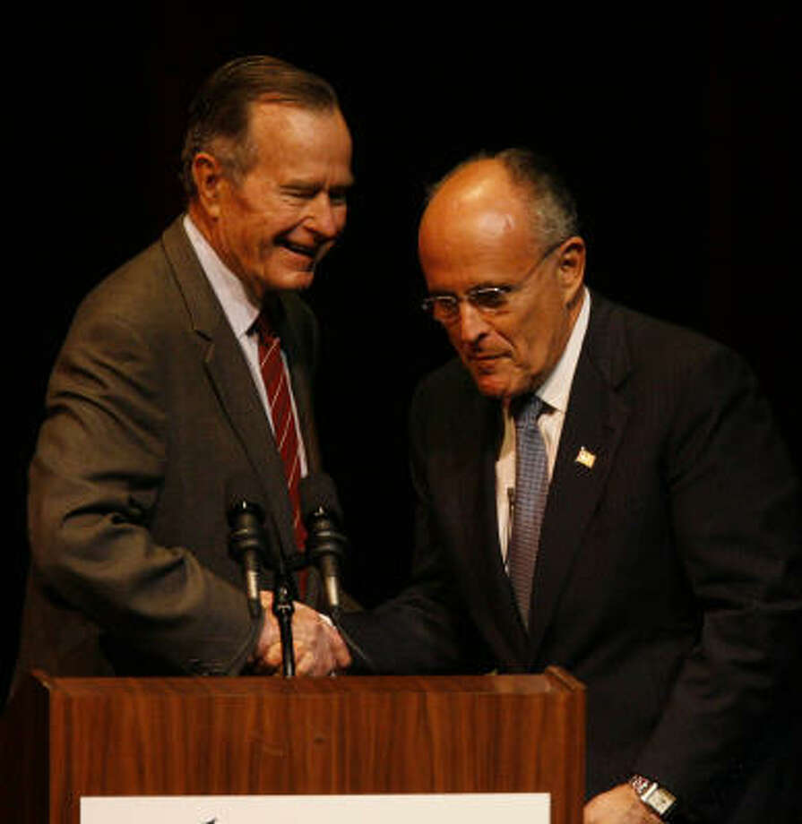 After an introduction speech, former President George Bush, left, shakes hands with GOP presidential frontrunner and former New York City mayor Rudy Giuliani at Texas A&M as part of the Wiley Lecture Series on Friday. Photo: Melissa Phillip, Chronicle