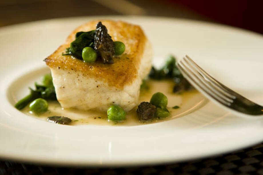 The halibut is bronzed to a crisp and accompanied by morels and peas. Photo: Nick De La Torre, Chronicle