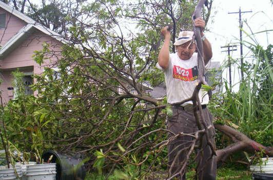 Felipe Ocampo, originario de México y habitante de Pasadena, corta las ramas del árbol que cayó en el patio de su casa y cuenta que no tuvo dinero para proteger sus ventanas con madera. Photo: Jorge Luis Sierra, La Voz