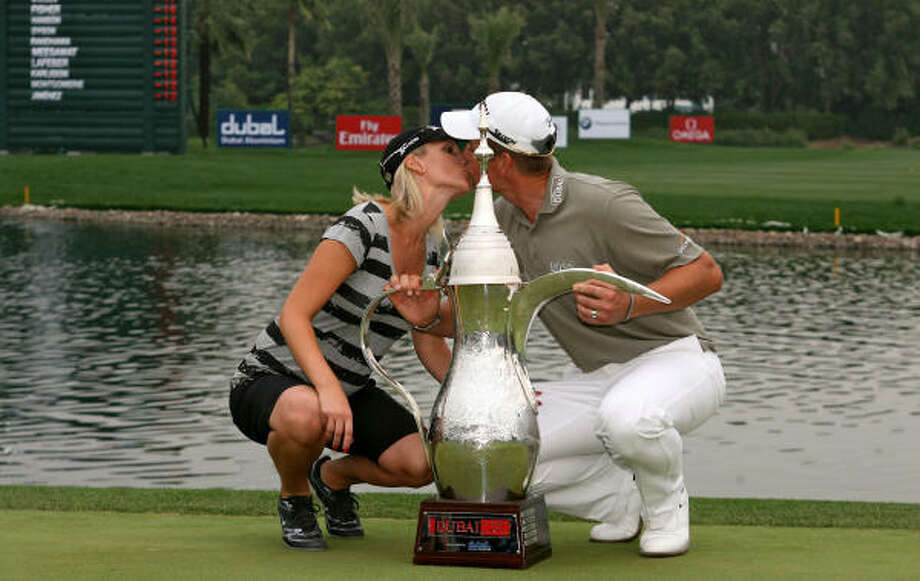 Henrik Stenson of Sweden kisses his wife Emma after beating back Tiger Woods and the rest of the field, not to mention a warm wind that kicked up sand and dust, to win the Dubai Desert Classic trophy. Photo: RABIH MOGHRABI, AFP/Getty Images