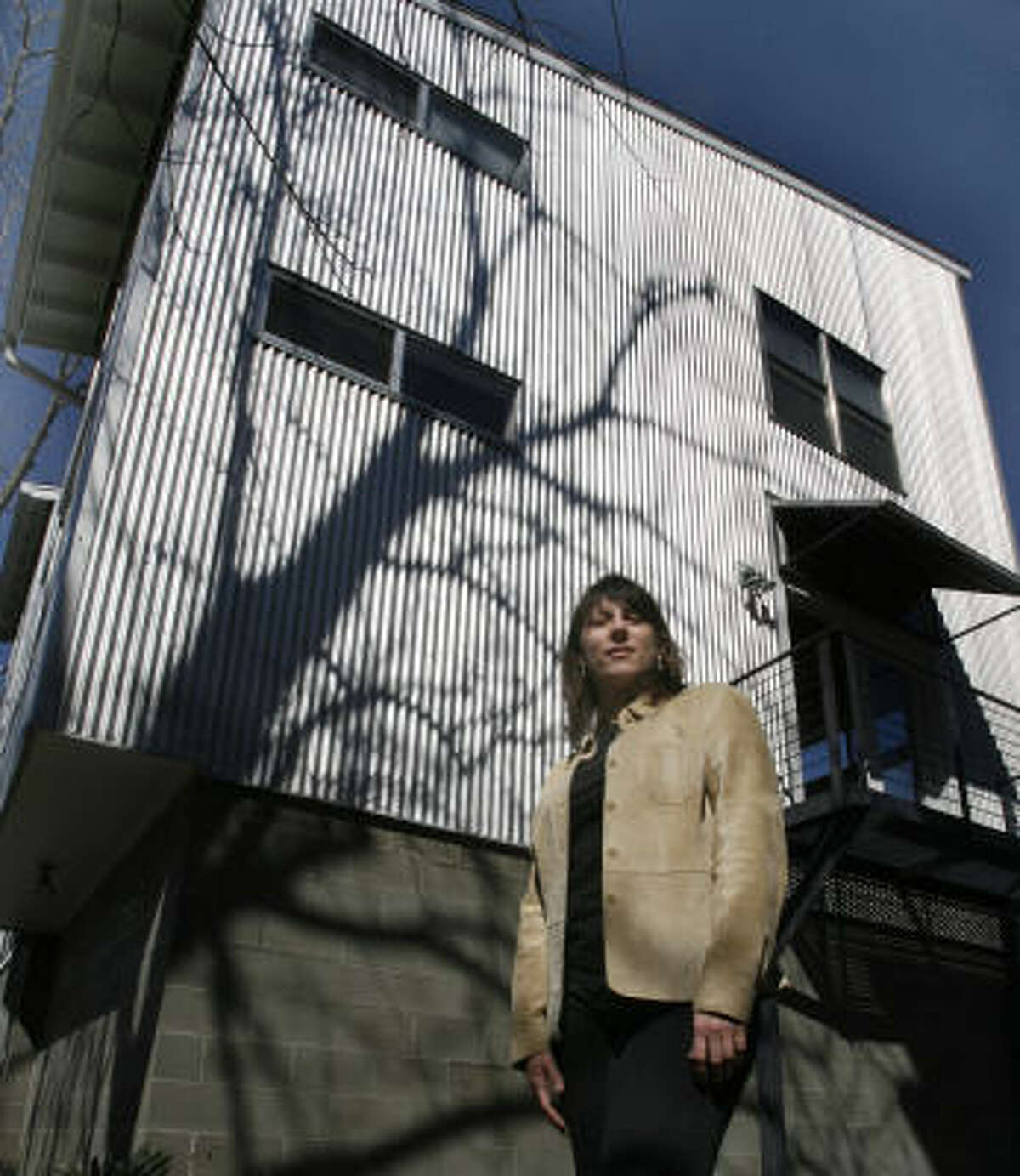 Architect Donna Kacmar stands outside her metal-clad home, which reflects the sun's heat, costs little, and looks beautiful as the sun sets.