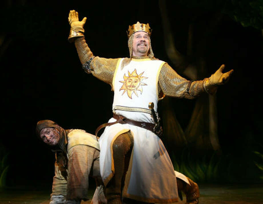 Patsy (Jeff Dumas) provides a makeshift throne for King Arthur (Michael Siberry) in Spamalot. Photo: Joan Marcus