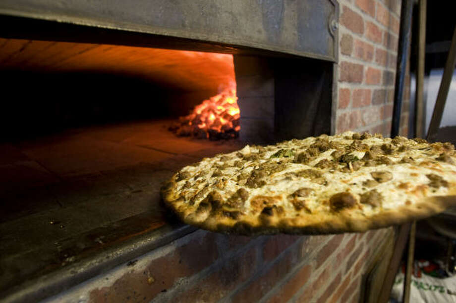 A white pizza with sausage and mushrooms emerges from the oven at Grimaldi's in Sugar Land. Photo: Johnny Hanson, Chronicle