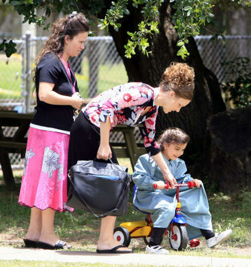 Caregivers at a group home in Liverpool tend to an FLDS child in June last year. Photo: Eric Kayne, Chronicle