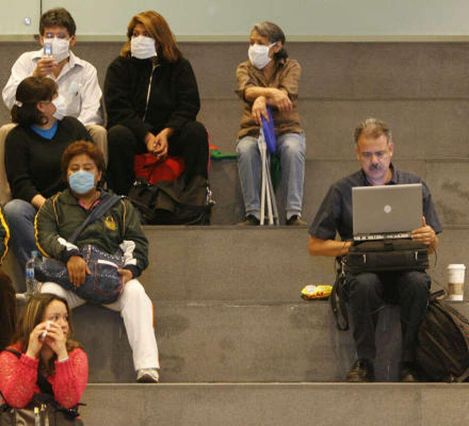 Passengers wait at Benito Juarez International Airport in Mexico City. Photo: Julio Cortez, Chronicle