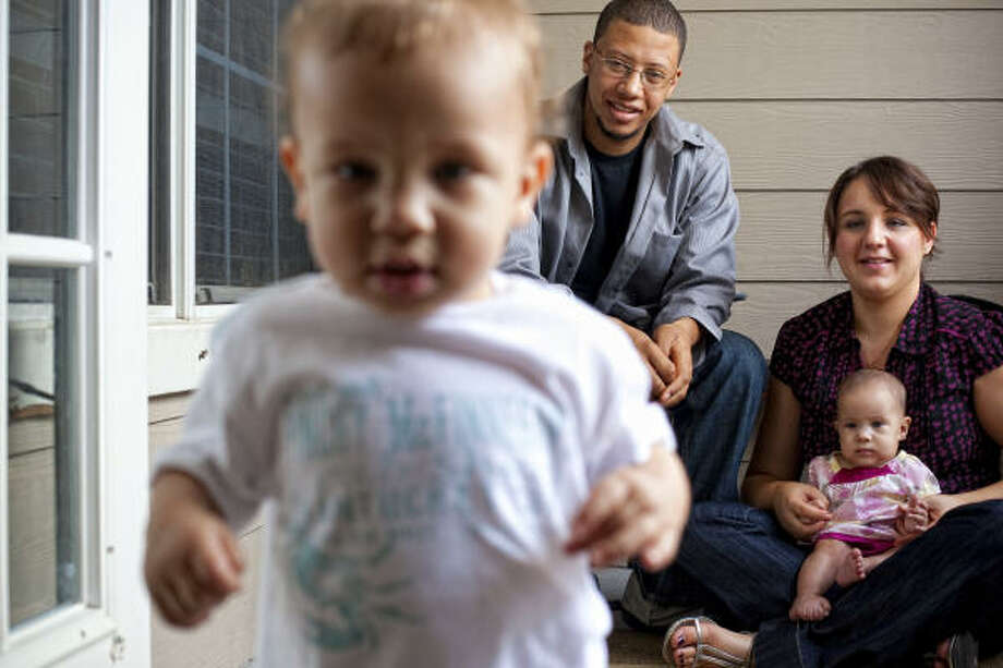 Monika and Cedric Washington and their 4-month-old daughter Zosia watch as 17-month-old Quenten plays on the balcony of their La Porte home last week. They made the decision this year to prevent any more pregnancies. Photo: Todd Spoth, ALL