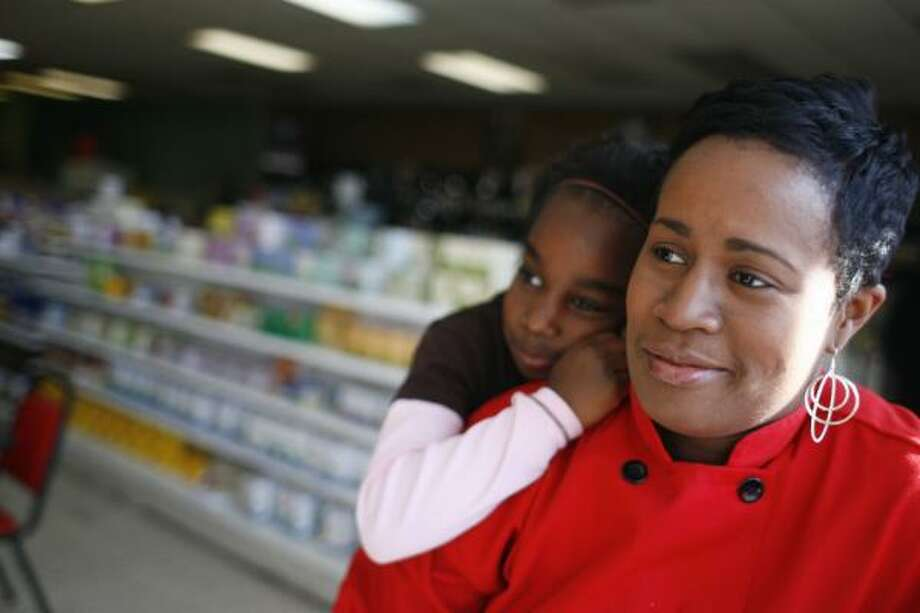 Arga Bourgeois and her daughter, Iman Smith, 7, spend time in her her store, Sunfired Foods, in Houston. Bourgeois was rejected by regular banks, but received a $13,000 microloan from Acción Texas and was able to expand her health food store in the Third Ward. Photo: SHARÓN STEINMANN, CHRONICLE