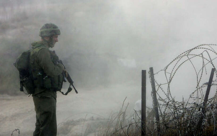 An Israeli soldier stands guard at the fence of the Israel-Lebanon border near the northern Israeli border town of Metulla on Thursday. Photo: DENIS SINYAKOV, AFP/Getty Images