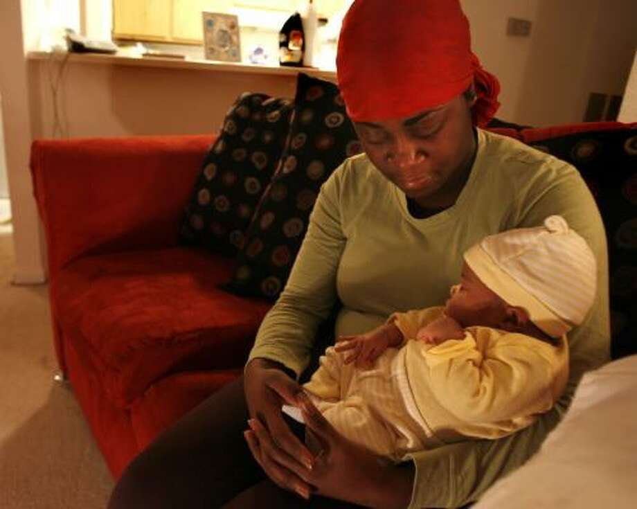 Kim Hines holds one-month-old daughter Kynadi La'Nae on Wednesday night and mourns the death of her husband, Jerry, who was killed while assisting motorists on U.S. 59. Photo: SHARÓN STEINMANN, CHRONICLE