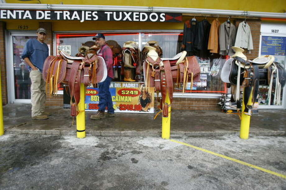 Alfonso Zavara, left, of Houston, and Kenneth Cox, of Bay City, look over charro-style saddles displayed in February in front of Scorpion's Western Wear in Pasadena. Photo: Nick De La Torre, CHRONICLE
