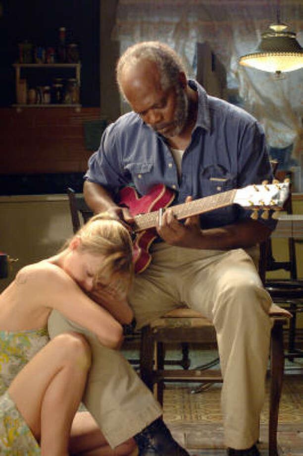 A farmer named Lazarus (Samuel L. Jackson) plays the guitar as Rae (Christina Ricci) listens in Black Snake Moan. Photo: Courtesy Photo