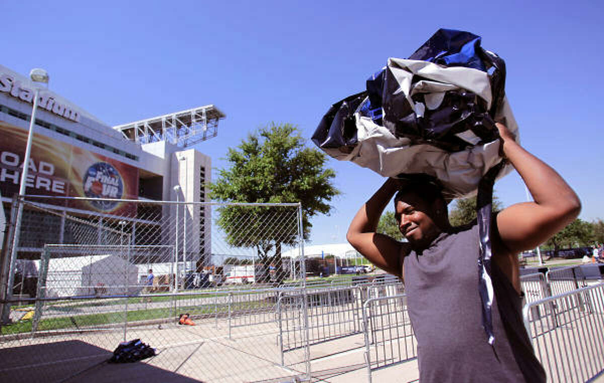Kendrick Taylor, of Corporate Installations, carries off a NCAA sign to be thrown out as he and others work to transform Reliant Stadium after the NCAA Final Four in Houston.