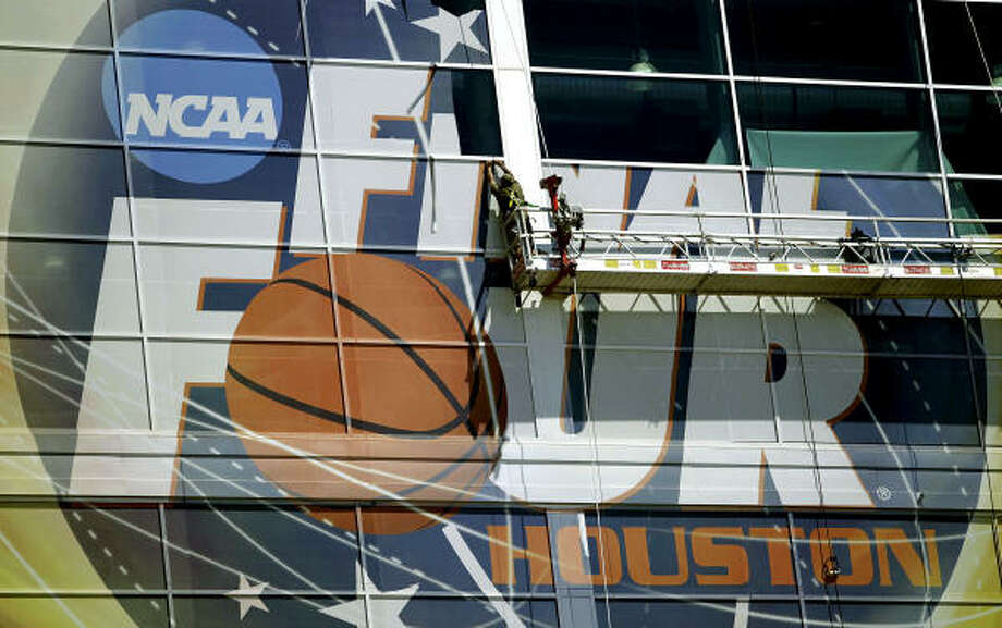 Workers peel off the Final Four sign off of Reliant Stadium. Photo: Karen Warren, Houston Chronicle
