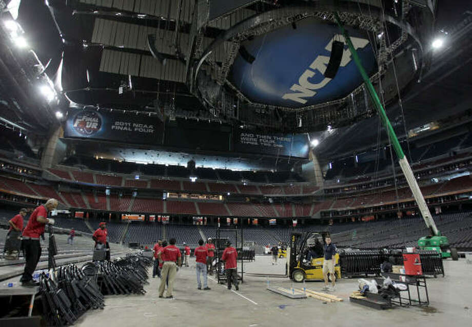 Workers transform Reliant Stadium after the NCAA Final Four.  The floor was pulled up earlier this morning. Photo: Karen Warren, Houston Chronicle