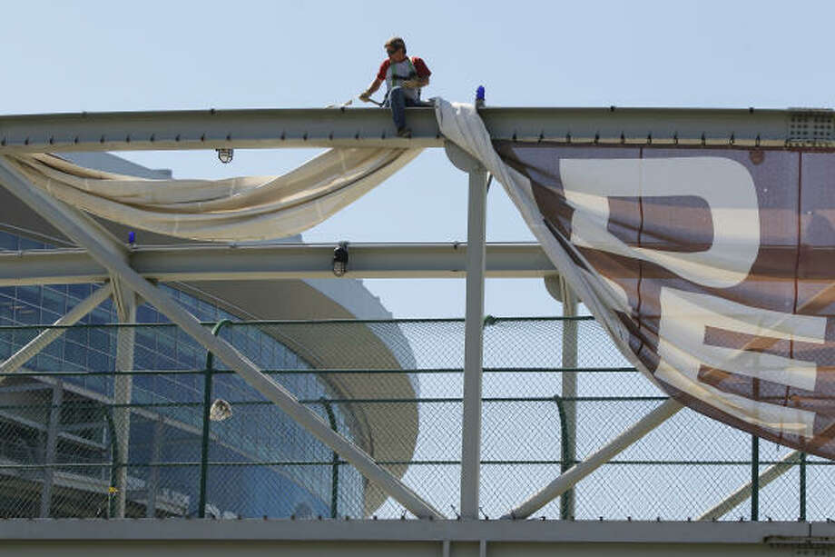 Mark Wallman with Hendee Enterprises takes down a Final Four banner on the pedestrian bridge over Kirby between Murworth and McNee. Photo: Melissa Phillip, Houston Chronicle