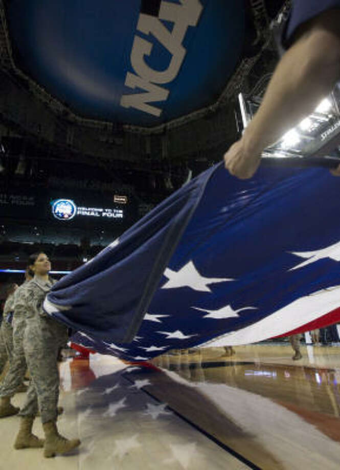 Members of the United States armed forces rehearse the unwrapping of the American Flag. Photo: Johnny Hanson, Houston Chronicle