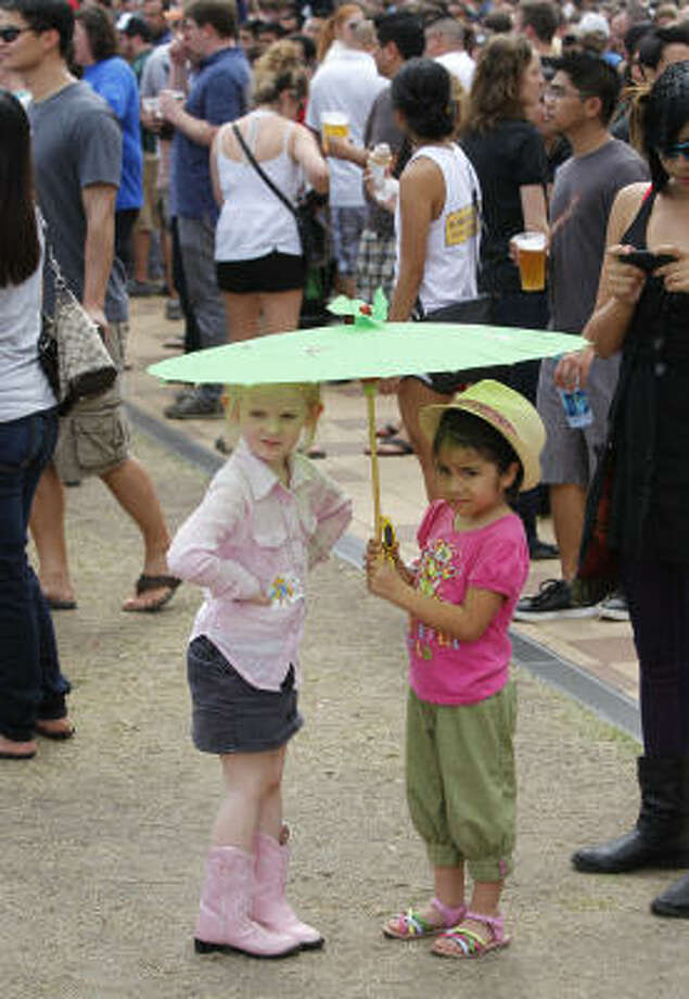 Victoria Harvey, 4, left, and her best friend, Angelina Vera, 5, right, both of Houston, have shade as they attend the Kings of Leon performance. Photo: Melissa Phillip, Chronicle