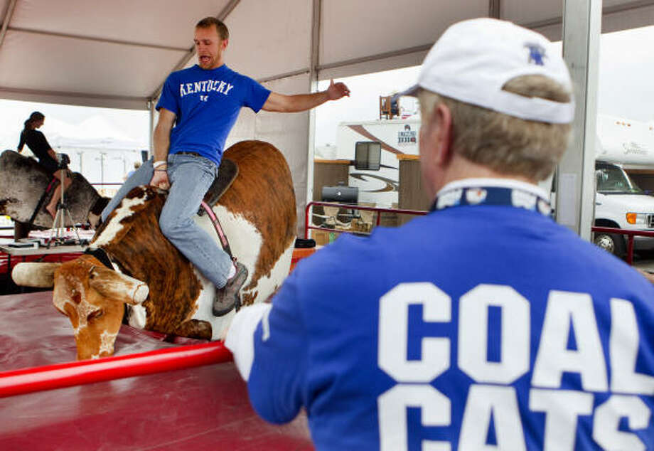 """Die-hard Kentucky fan,"" Brian Morgan, 22, rides a mechanical bull at the NCAA Final Four Tip-Off Tailgate outside Reliant Stadium before the national semifinals. Photo: Johnny Hanson, Chronicle"