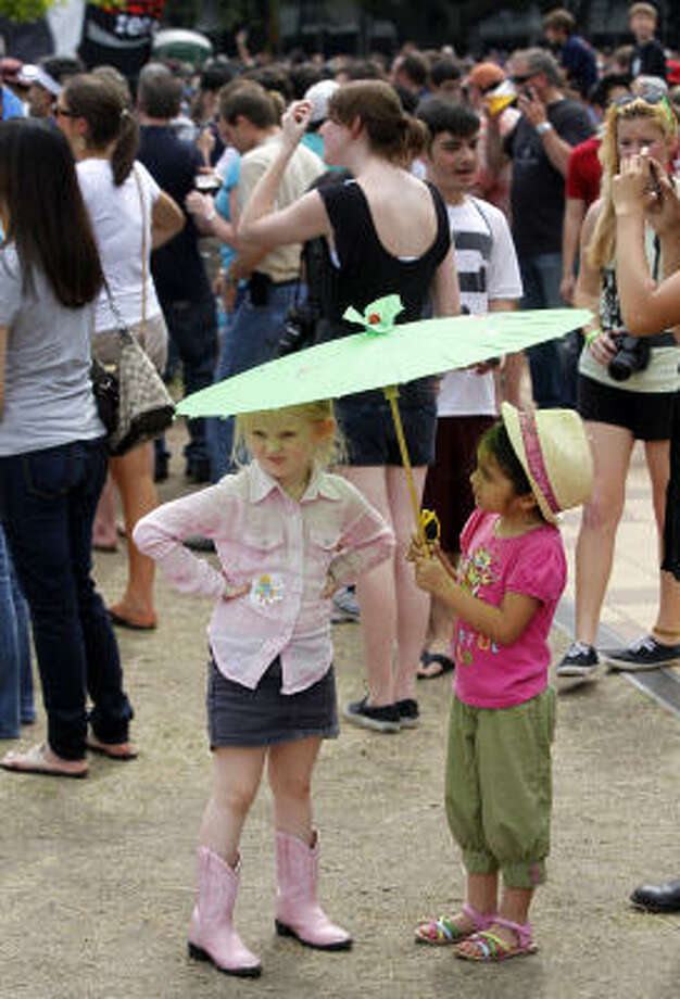 Victoria Harvey, 4, left, and her best friend, Angelina Vera, 5, right, both of Houston have shade as they attend the Kings of Leon performance at the Big Dance Concert series at Discovery Green. Photo: Melissa Phillip, Houston Chronicle