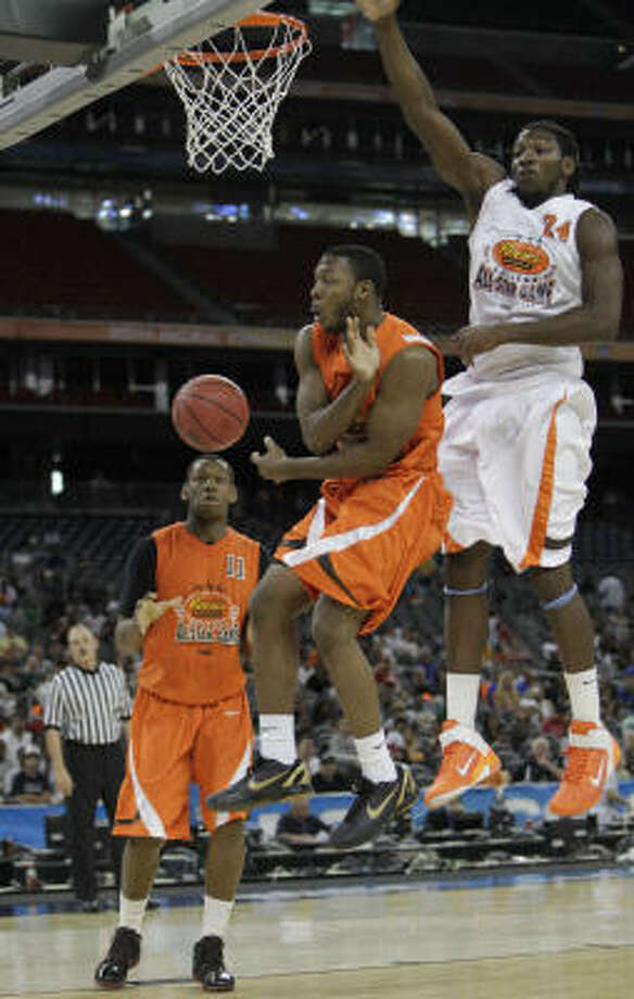 East guard Jacob Pullen of Kansas State (3) wraps a pass around his body to East forward Lavoy Allen of Temple (11) as West forward Kenneth Faried of Morehead State (24) defends during the second half of the Reese's College All-Star Game. Photo: Karen Warren, Houston Chronicle