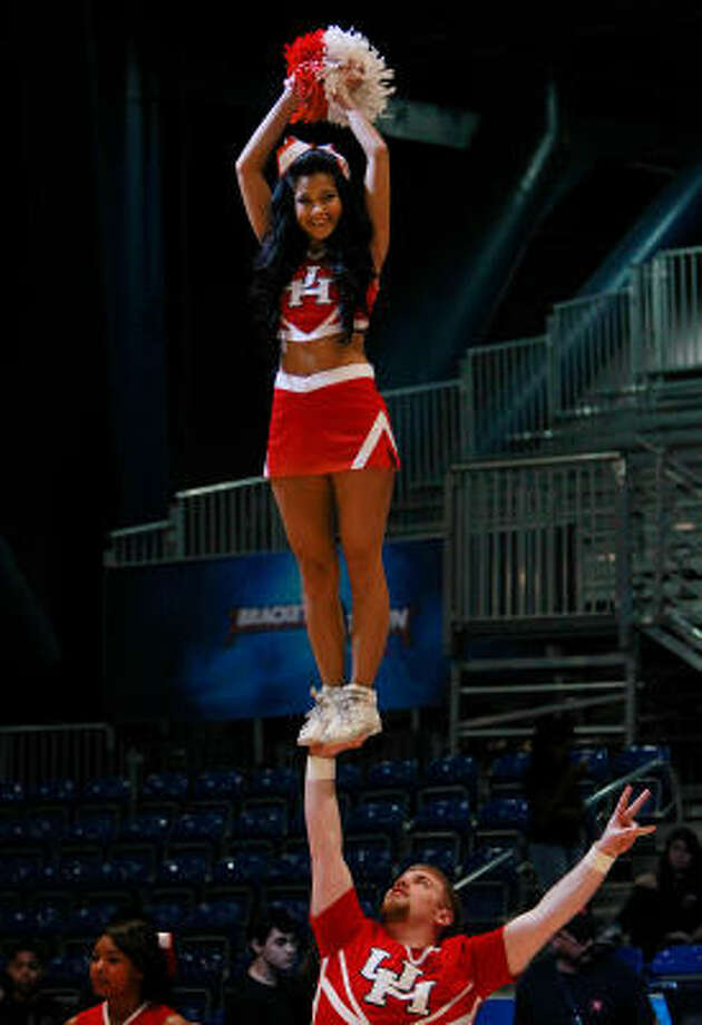 UH cheerleader Franky Benavidez performs a difficult stunt during Thursday's opening of Bracket Town. Photo: Mayra Beltran, Chronicle