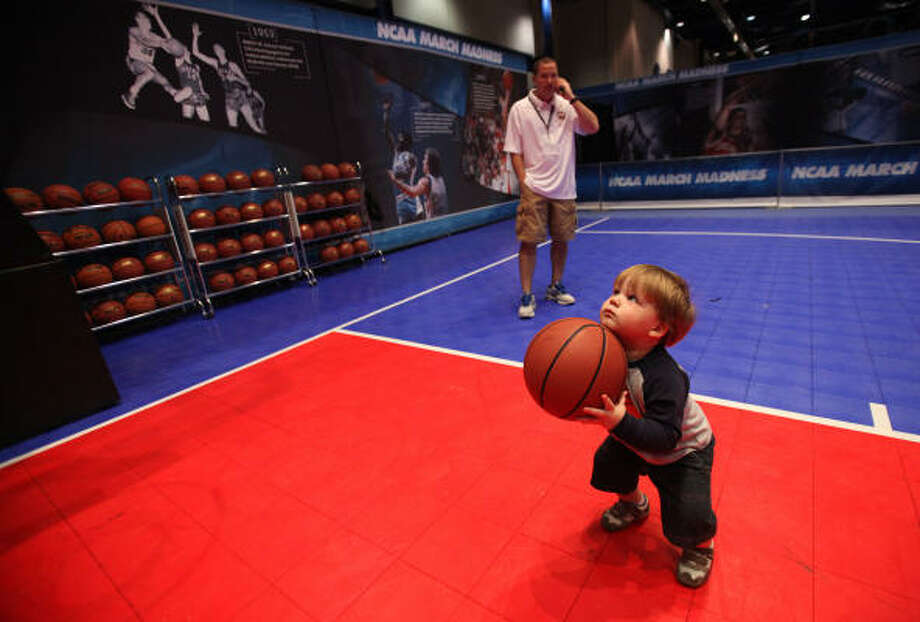 Hayden Burleson, 1, attempts to score at a basketball court in Bracket Town. Photo: Mayra Beltran, Chronicle
