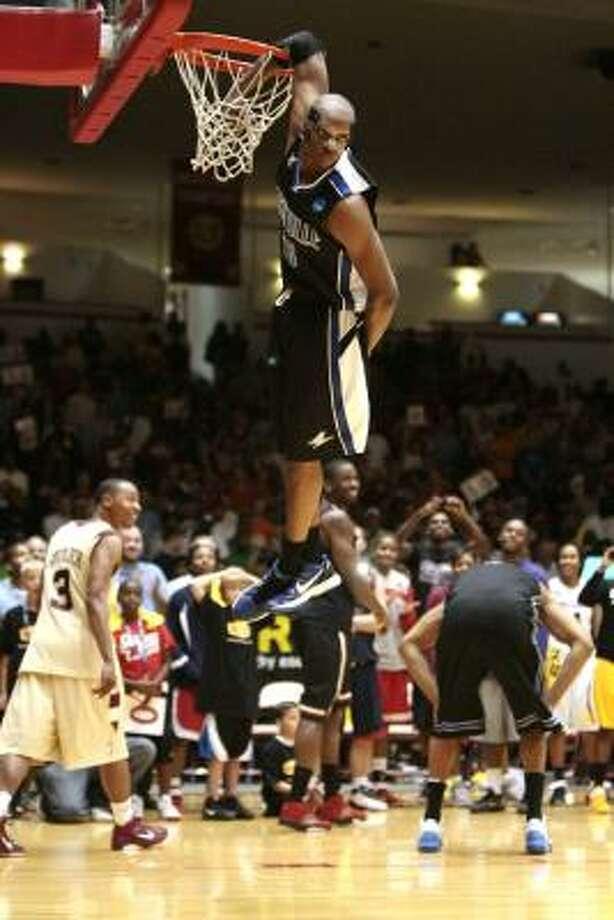 UNC-Ashville's John Williams hangs from the rim after finishing a dunk. Photo: Billy Smith II, Chronicle