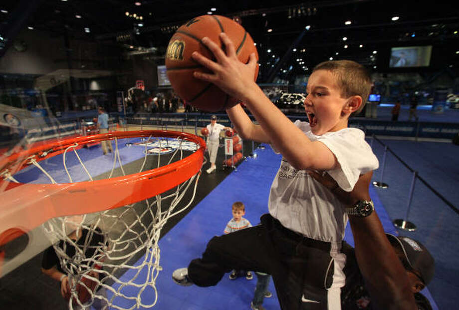 Davis Young, 8, gets help to dunk in the Slam Dunk Competition court in Bracket Town at the George R. Brown Convention Center on Thursday, March 31, 2011, in Houston.  Basketball courts sponsored by various companies host competitions, give-aways, and basketball pointers from coaches. Photo: Mayra Beltran, Chronicle