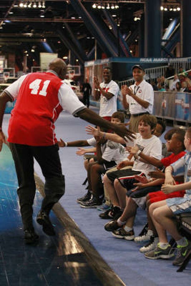 Clyde Dexter high-fives children seating in the VIP chairs after scoring a 3 pointer during the HORSE competition at Bracket Town at the George R. Brown Convention Center on Thursday, March 31, 2011, in Houston. Photo: Mayra Beltran, Chronicle