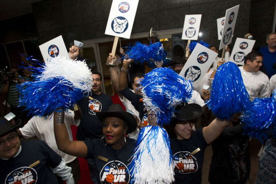 A cheering section of Sheraton Suites employees wave pom poms, ring cow bells and waves signs as the