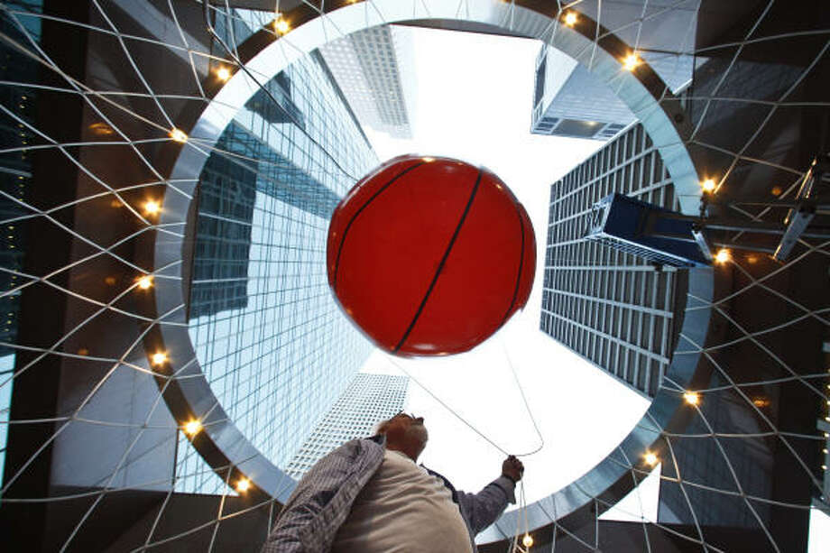 Creative Director of Sherrariums Company, Stephen McCrary, holds a guide rope attached to a 10ft diameter inflatable basketball as they hang it in the center of a 36ft diameter basketball net installed at the Wells Fargo Plaza in Houston.  McCrary was hired to install the art work for the upcoming NCAA Final Four Tournament in Houston. Photo: Michael Paulsen, Houston Chronicle