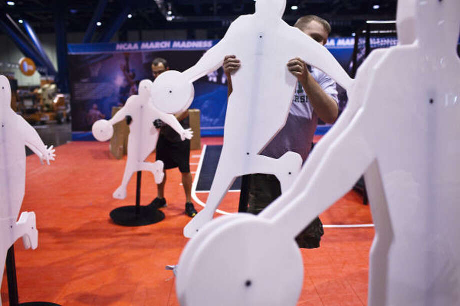 Todd Alles, left, and Aaron Wallce move around silhouettes during the installation and build out of Bracket Town in preparation for the ultimate fan fest opening on Thursday, March 31 at the George R. Brown Convention Center. Photo: Eric Kayne, For The Chronicle