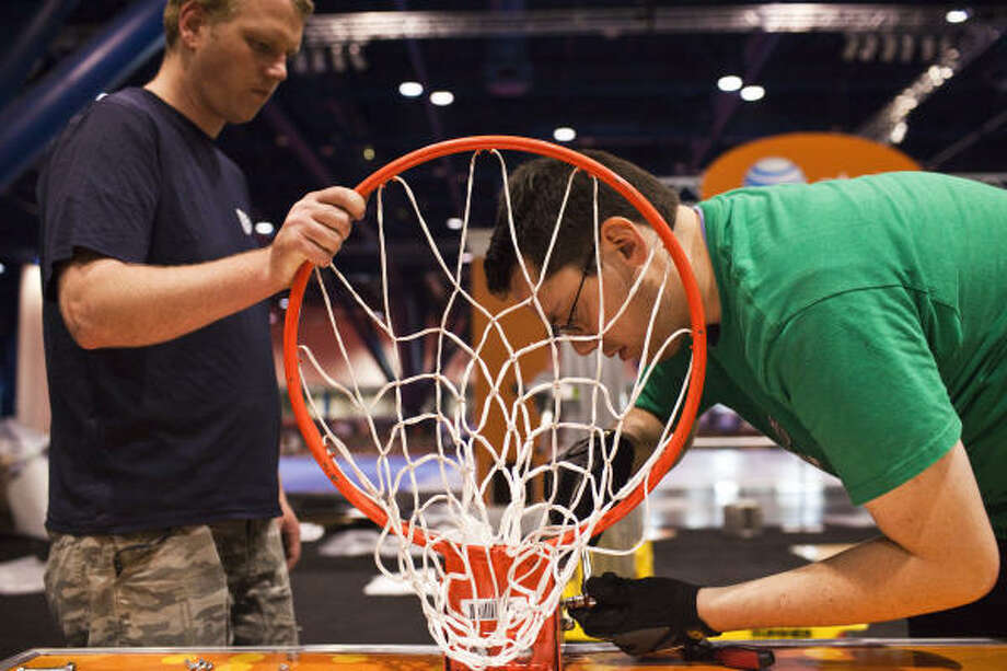 Andrew Knutson, left, and Adam Ahern assemble a basketball hoop at one of the event booths during the installation and build out of Bracket Town in preparation for the ultimate fan fest opening on Thursday, March 31. Photo: Eric Kayne