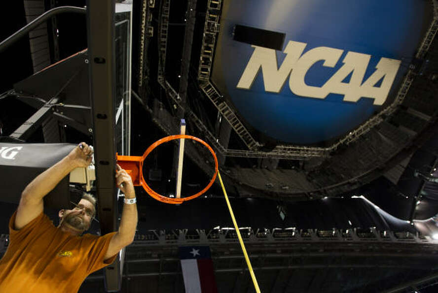 Billy Holt, of Spalding, sets up one of the backboards while working to get the Final Four court rea
