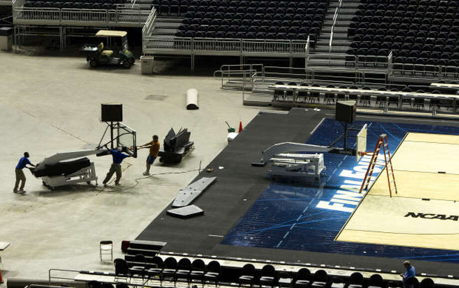 Michael Miles, left, Lorenzo Warren, center, and Billy Holt move a spare backboard across the floor at Reliant Stadium while the finishing touches on the playing surface are installed for the Final Four Monday, March 28, 2011, in Houston. Photo: Brett Coomer, Houston Chronicle