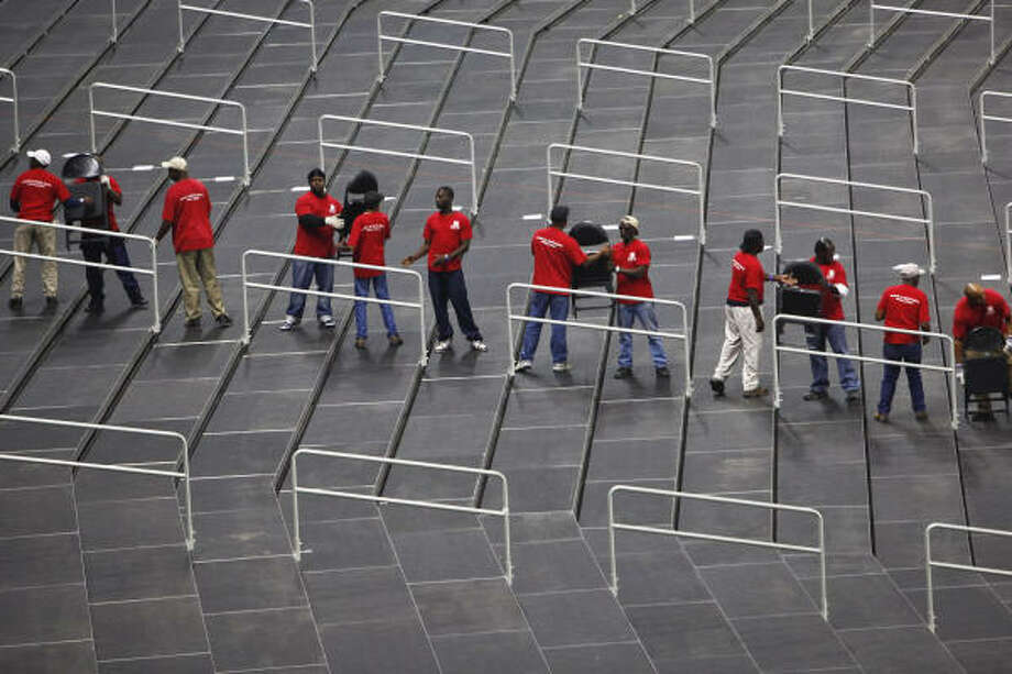Workers install chairs while another group installs the wood flooring (232 pieces weighing 400lbs each) at Reliant Stadium in preparation for the upcoming Final Four Basketball Tournament in Houston. Photo: Michael Paulsen, Chronicle