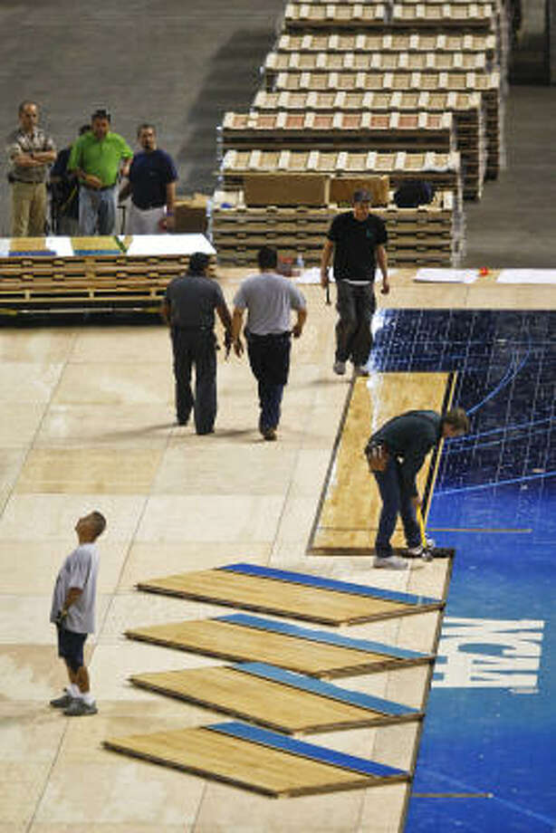 Bruce Haroldson, head installation technician for Connor Sport Court Int., works to install the wood flooring (232 pieces weighing 400lbs each) at Reliant Stadium in preparation for the upcoming Final Four Basketball Tournament, Friday, March 25, 2011, in Houston. Photo: Michael Paulsen, Chronicle