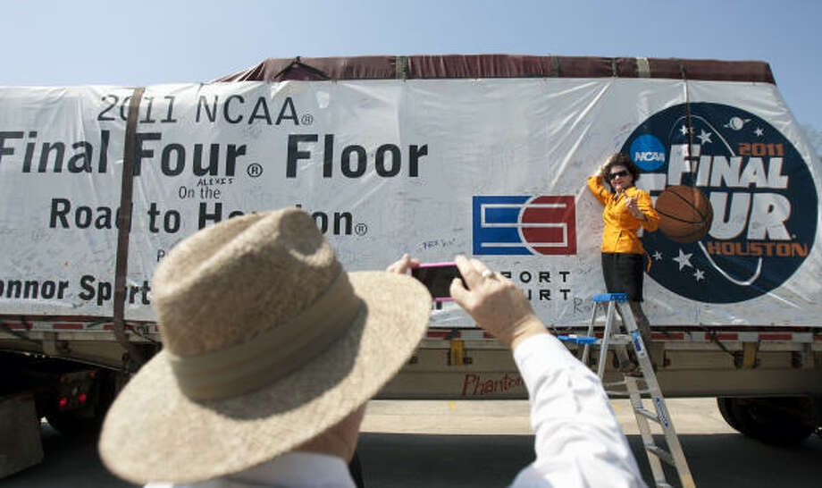 """Rob Way takes a photo of co-worker, and Longhorns fan, Sandra Tetley after she signed a banner hanging on the side of a 40-foot flat bed trailer containing the 2011 playing surface of the Men's NCAA Final Four Championship at the Lyndon B. Johnson Space Center Visitor Center Thursday, March 24, 2011, in Houston. """"I was gonna write 'Texas was robbed',"""" Tetley said laughingly. """"But, I didn't want to be a sour grape."""" The public was invited to come and see the truck and sign the truck banner that will be traveling to Reliant Stadium. The court has made its way from Salt Lake City where the manufacturer of the playing surface, Connor Sport Court International, is headquartered. Stops honoring NCAA colleges and teams have been made along the way. Photo: Cody Duty, Houston Chronicle"""