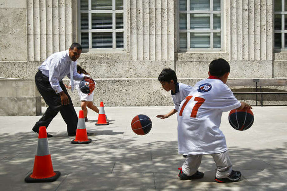 Council Member Jarvis Johnson watches as Aron Lopez, 8, and Jacob Rich, 7, practice their dribbling skills during the Houston Local Organizing Committee (HLOC) for the NCAA Men's Final Four event in front of City Hall that attracted 22 third-graders from Briarmeadow Charter School, Wednesday, March 23, 2011, in Houston. Photo: Michael Paulsen, Chronicle