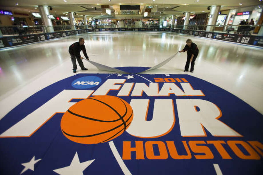 "Gray and Kim Johnson, both ice skating coaches at Memorial City mall, install the NCAA Final Four logo at the ice rink March 6, 2011 at the Galleria in Houston, TX. Gray said he and his wife would be at the mall until about 2:00 am to 3:00 am coating the logo with water until the ice becomes at least 1/8"" thick. After, it'll need to be coated by others until the ice is 1 1/2"" thick, when it'll be safe to skate over. Gray Johnson has been creating ice rink logos for 15 years. He made the NCAA logo in his garage where it was hand drawn and then painted over. Photo: Eric Kayne, For The Chronicle"