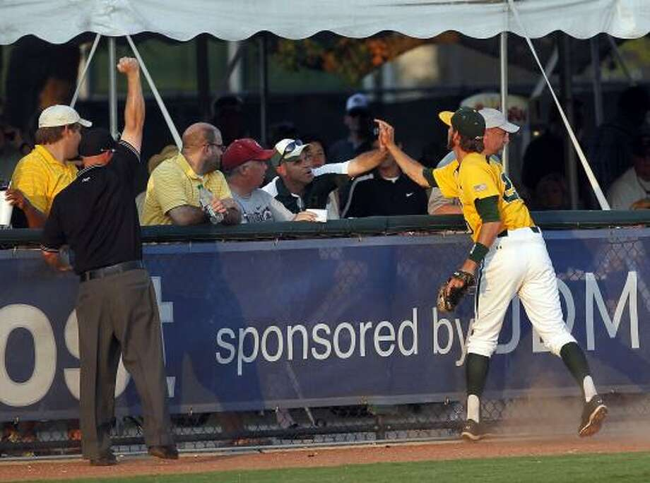 Baylor's Jake Miller gives a Baylor fan a high-five after catching a fly ball in foul territory during the seventh inning as Baylor University defeated Rice University 3-2. Photo: Johnny Hanson, Houston Chronicle
