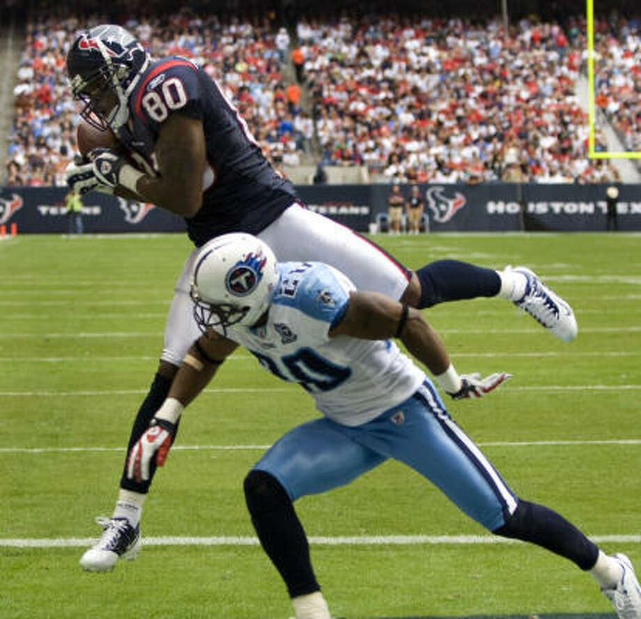 Texans wide receiver Andre Johnson (80) pulls down a 13-yard touchdown reception over Tennessee Titans defensive back Chris Carr in the second quarter of Sunday's game at Reliant Stadium. Photo: Brett Coomer, Chronicle