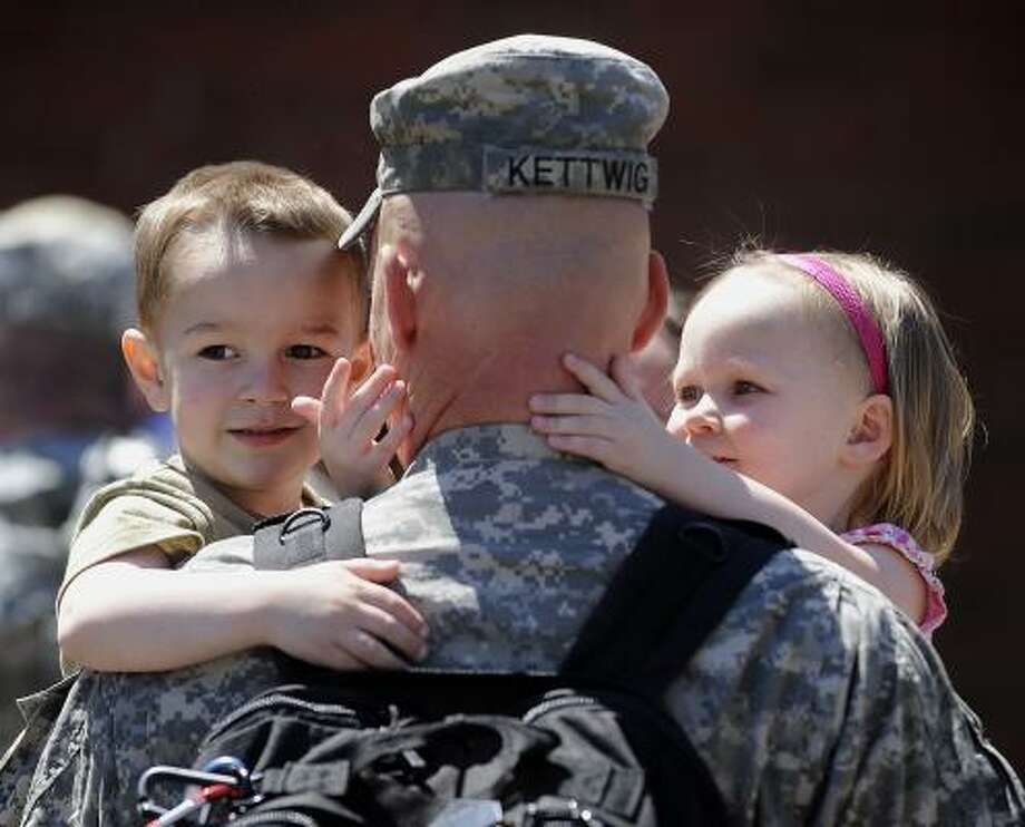 Who: Major Jason Kettwig of Milbank, S.D.. Where:  Augustana College, Sioux Falls, S.D. When: May 3, 2011.  Details: The Army National Guard officer greets his 4-year-old son, Ty, and his 2-year-old daughter, Jocelyn. Photo: Elisha Page, Argus-Leader