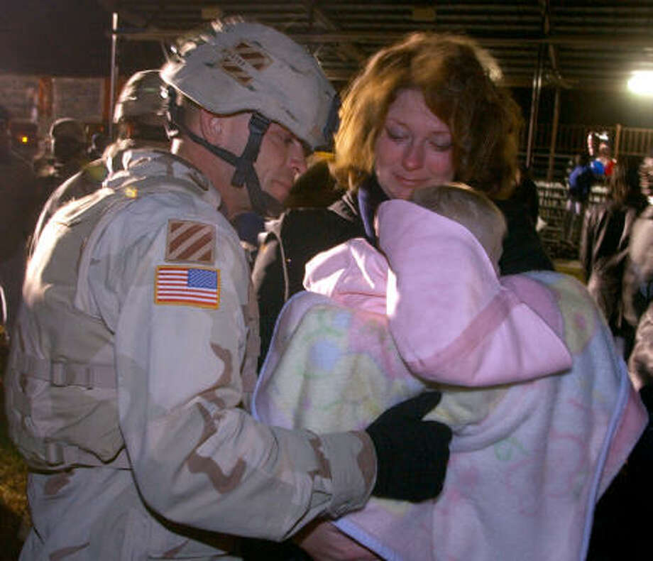 Who: Army Spc. William Buckey and his wife, Jodi, and infant daughter.  Where:  Fort Stewart, Ga. When: Dec. 2, 2005. Photo: STEPHEN MORTON, AP