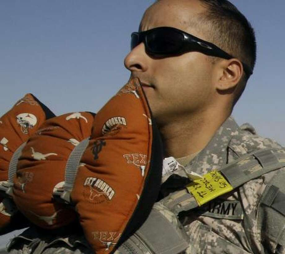 Who: Sgt. Frank Sanchez of Austin. Where:  Baghdad. When: Dec. 3, 2010.  Details: That's a University of Texas pillow he's carrying for an 18-hour flight. Photo: Maya Alleruzzo, AP