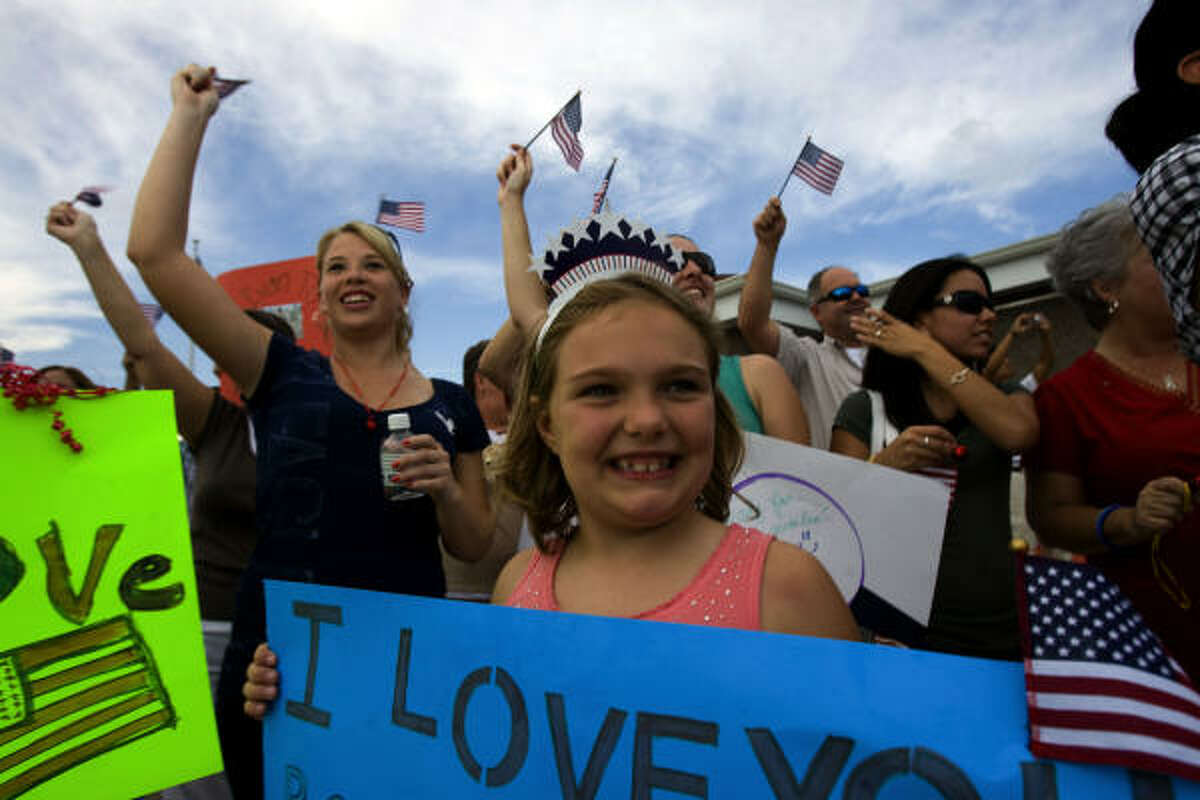 Tavin Wampler, 8, niece of Marine Cpl. Ryan Wampler, 24, of Katy holds a sign that says